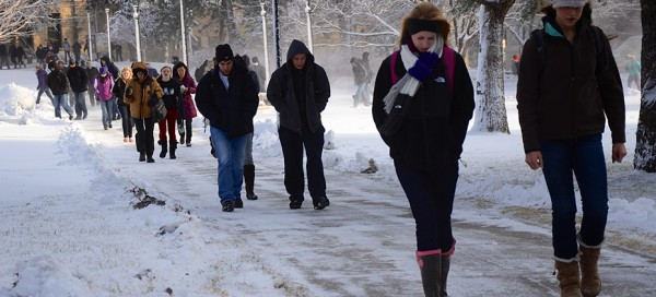 Students walk to class through snow day after temperatures break 70s