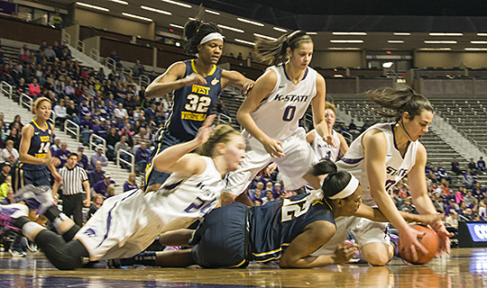 (Photo by Emily DeShazer | Collegian)  Wildcats and Mountaineers dive for a loose ball during K-State's 61-40 loss to West Virginia Saturday in Bramlage Coliseum.