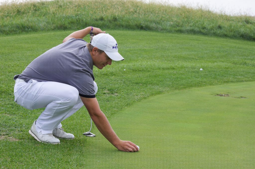 Ben Fernandez, then-senior in finance, carefully aligns his putt during a Friday afternoon practice at Colbert Hills Country Club on Oct. 5, 2018. Before playing 18 holes, Fernandez works on perfecting his short game before playing a practice round. (File photo by Brooke Barrett | Collegian Media Group)