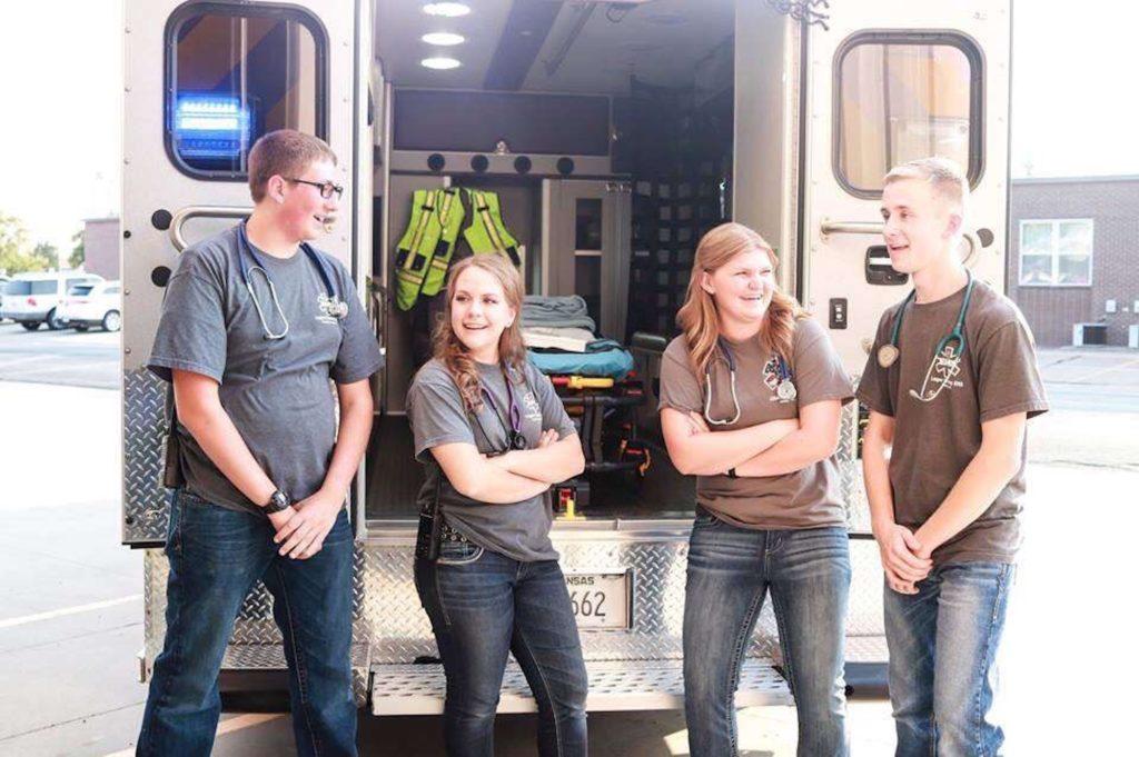Kourtney Rumback and her friends pose beside an ambulance. (Photo courtesy of Kourtney Rumback)