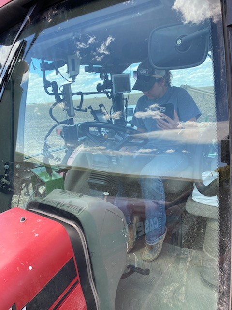 Zoe Shultz attends a Zoom class while helping with planting on her family's farm. Shultz said it is challenging, but luckily the tractor has auto-steer and she can pay attention to class. (Photo courtesy of Zoe Shultz)