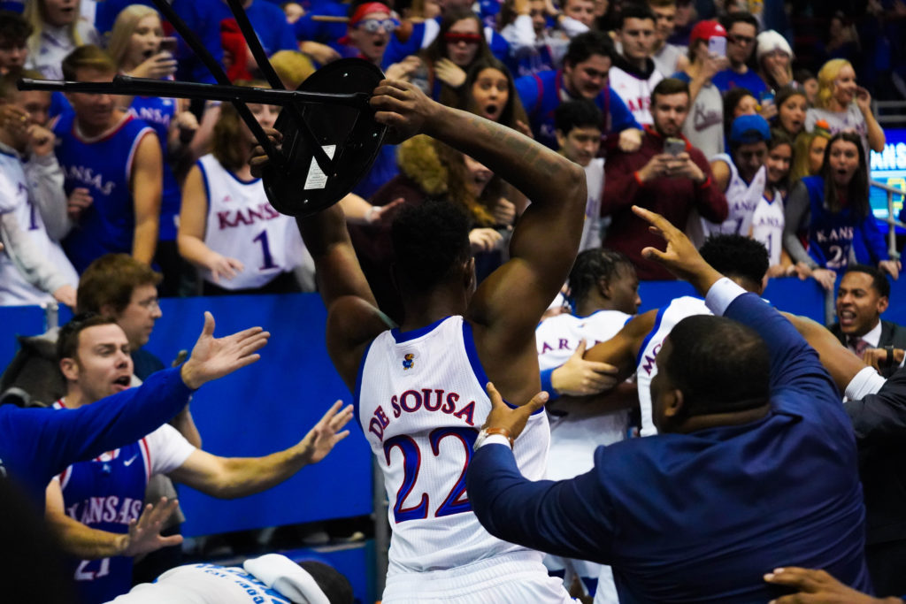 Kansas assistant men's basketball coach Jerrance Howard and courtside bystanders successfully stop Kansas sophomore forward Silvio De Sousa from using a stool in the brawl that broke out in Lawrence during the first Sunflower Showdown of the season. The Wildcats fell to the Jayhawks 81-59.  (Luis Villarreal-Reyes | Collegian Media Group)