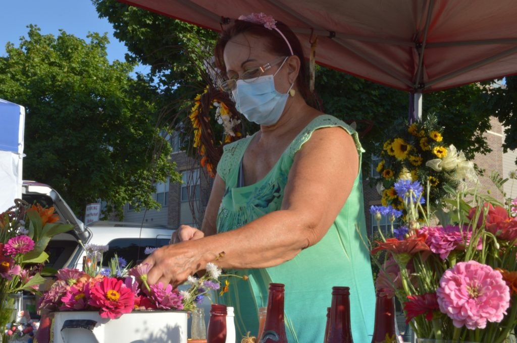 Shirley York arranges a vase of flowers at her tent on Saturday morning.