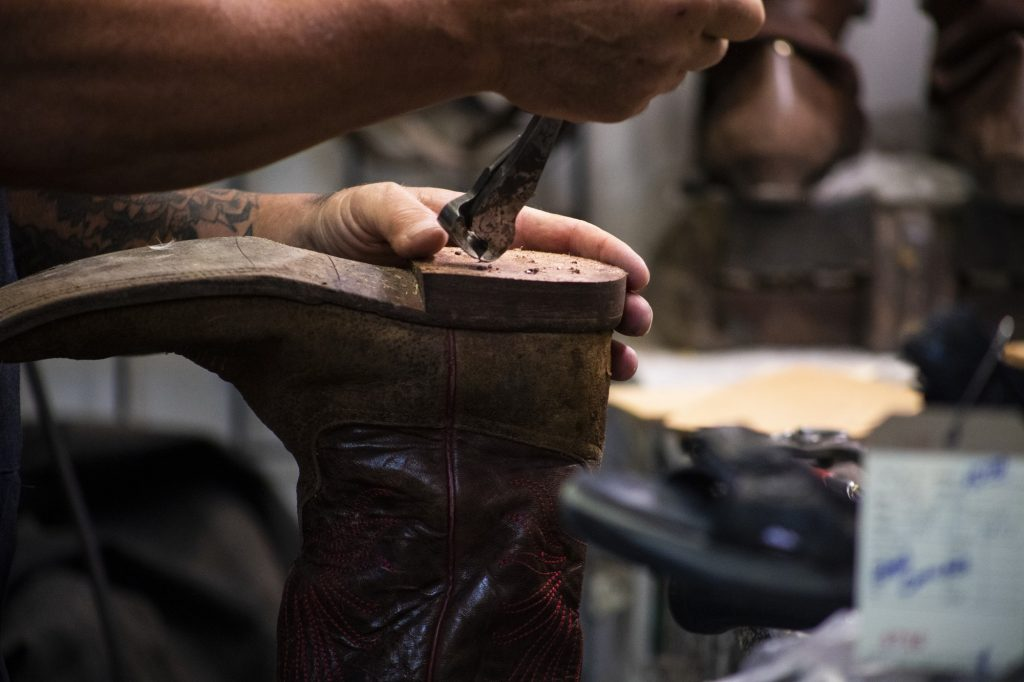 Edwin Olson Jr. mends the sole of a cowboy boot