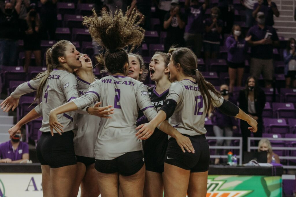 The Wildcats celebrate after scoring the final point against Iowa State to win the match 3-1 earlier this season. (Sophie Osborn | Collegian Media Group)