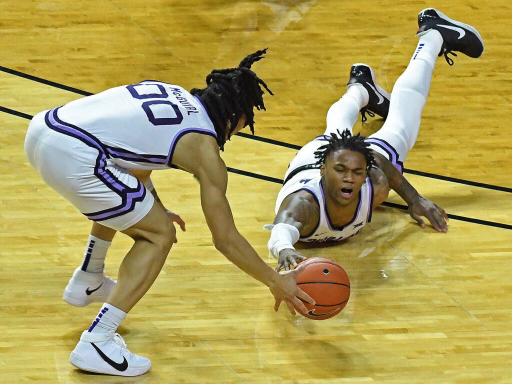 K-State sophomore guard DaJuan Gordon dives for the basketball as senior guard Mike McGuirl steps in to help in K-State's 69-47 loss to West Virginia on Jan. 23. (Photo Courtesy of Scott Weaver)