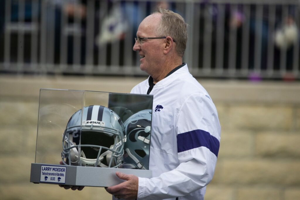 Athletic Director Gene Taylor awards Larry Moeder a helmet prior to K-State's 24-20 loss to West Virginia on Nov. 16, 2019. Taylor recently agreed to terms with a contract extension that will keep him at K-State through the 2026-27 academic year. (Dalton Wainscott I Collegian Media Group)