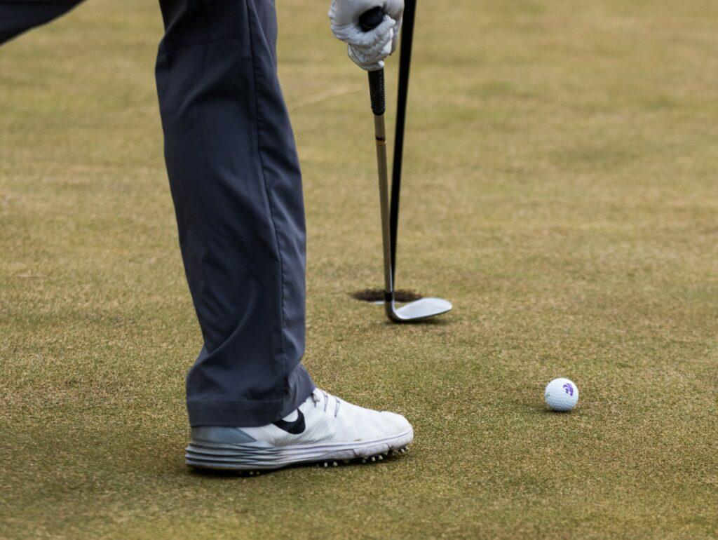 A K-State Men's Golf player, picks up a golf ball at Colbert Hills Golf Course on Mar. 9, 2017. (John Benfer | Royal Purple)