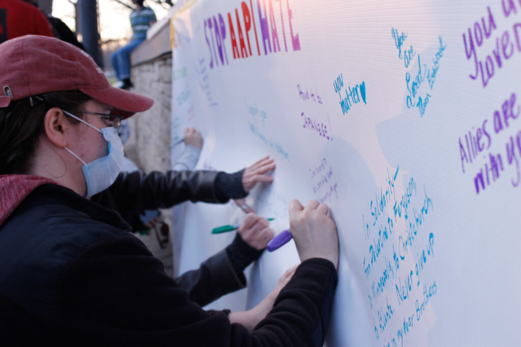 At the end of the vigil, community members were invited to come down and write a message of solidarity on a banner spread across the front of the stage in City Park. (Kaylie McLaughlin | Collegian Media Group)